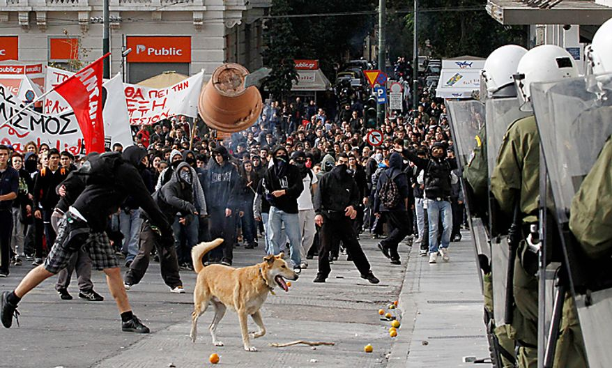 A protester throws a plant pot at riot police during a rally in Athens on Monday, Dec. 6, 2010. Youths hurled rocks and oranges at a government building in central Athens during a student protest to mark two years since the fatal police shooting of a teenage boy that sparked Greece's worst riots in decades. Police closed roads and deployed several thousand officers around the city but maintained a minimal presence at the site where some 1,500 students gathered outside Athens University's main buildings. (AP Photo/Alkis Konstantinidis)