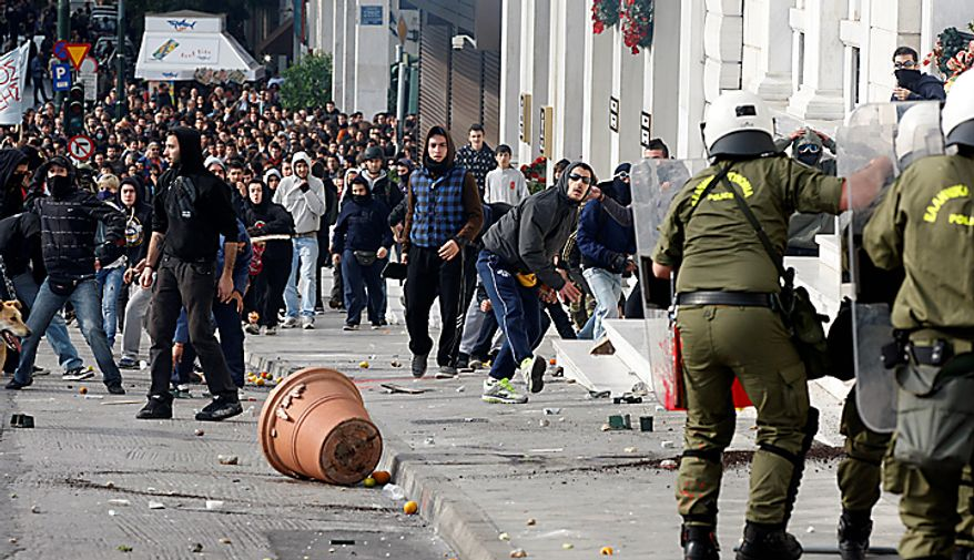 Youths throw stones at riot police during a rally in Athens on Monday, Dec. 6, 2010. The protest mared two years since the fatal police shooting of a teenage boy that sparked Greece's worst riots in decades. Police closed roads and deployed several thousand officers around the city but maintained a minimal presence at the site where some 1,500 students gathered outside Athens University's main buildings. (AP Photo/Thanassis Stavrakis)