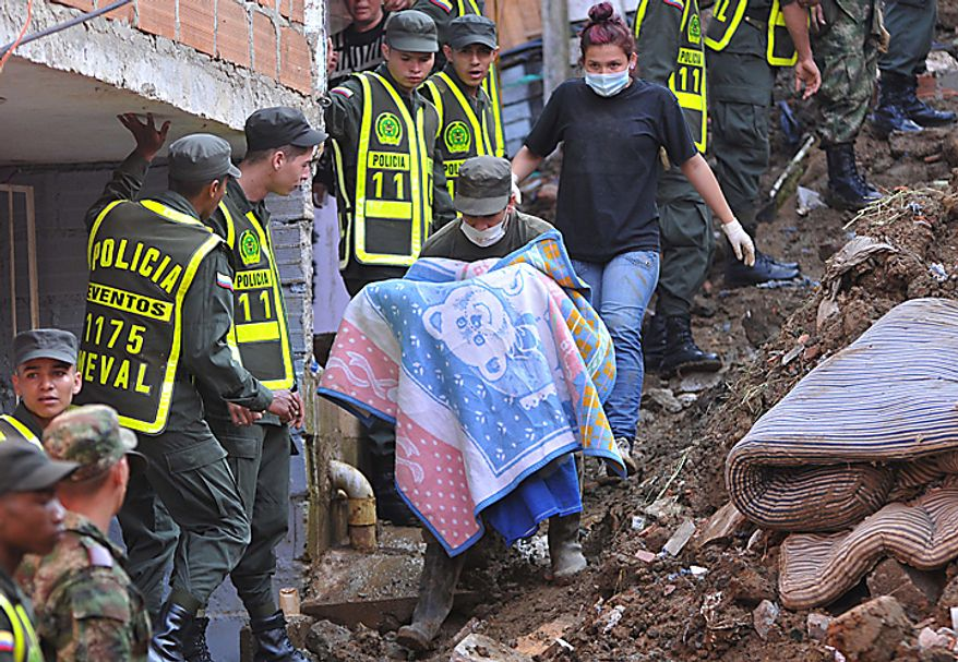 A police officer carries the body of a girl, covered in a blanket, at the site where a landslide buried houses trapping dozens beneath mud and rubble following weeks of drenching rains, in Bello, northwestern Colombia, Monday, Dec. 6, 2010. At least 12 bodies were dug out of the mud. The Red Cross attributes more than 180 deaths to floods and landslides caused by heavy rains in Colombia so far this year. (AP Photo/Luis Benavides)