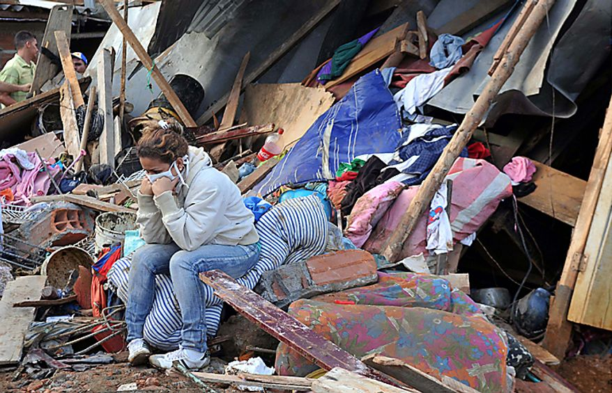 A woman sits in front of her home, destroyed by a landslide that buried dozens of houses and left dozens trapped beneath mud and rubble following weeks of drenching rains in Bello, northwestern Colombia, Monday, Dec. 6, 2010. At least 12 bodies were dug out of the mud. The Red Cross attributes more than 180 deaths to floods and landslides caused by heavy rains in Colombia so far this year. (AP Photo/Luis Benavides)