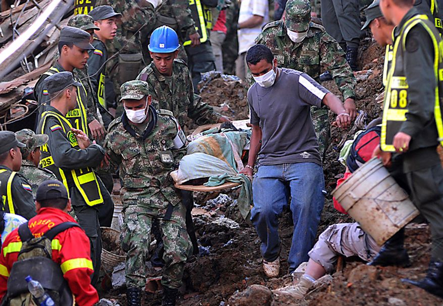 Soldiers and a resident carry a body recovered from the site where a landslide buried houses trapping dozens beneath mud and rubble following weeks of drenching rains in Bello, northwestern Colombia, Monday,  Dec. 6, 2010. At least 12 bodies were dug out of the mud. The Red Cross attributes more than 180 deaths to floods and landslides caused by heavy rains in Colombia so far this year. (AP Photo/Luis Benavides)