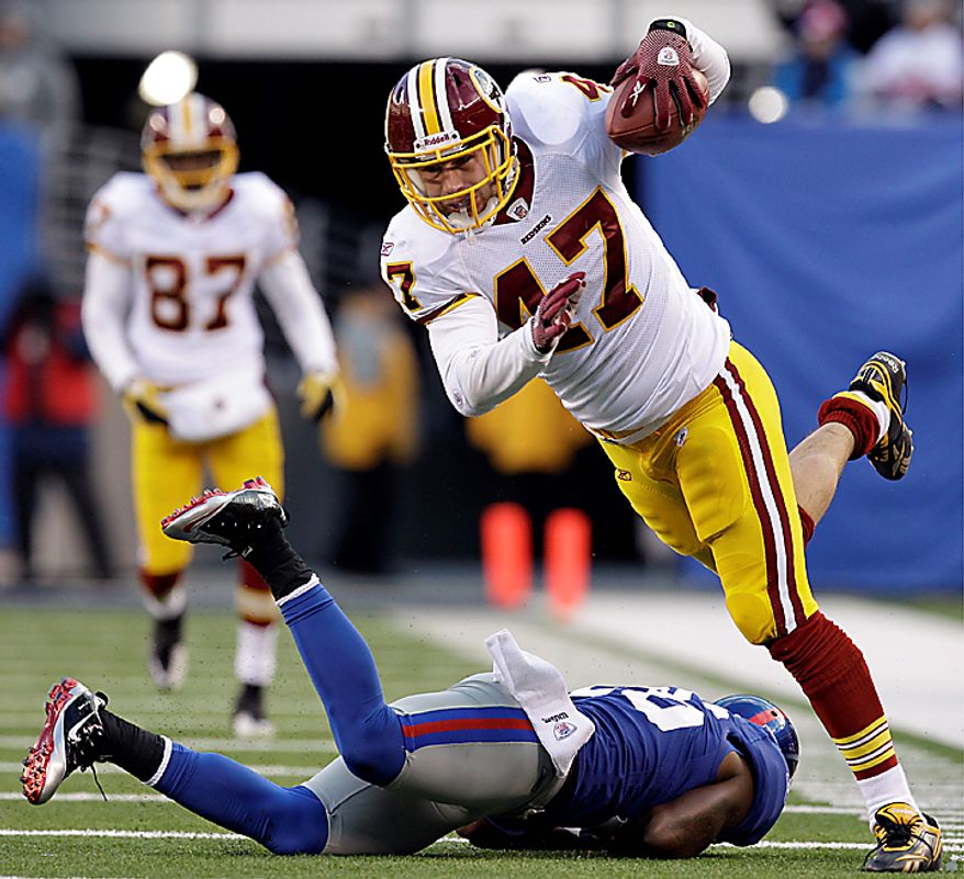 Washington Redskins tight end Chris Cooley (47) avoids a tackle by New York Giants safety Antrel Rolle (26) during the fourth quarter of an NFL football game at New Meadowlands Stadium, Sunday, Dec. 5, 2010, in East Rutherford, N.J. (AP Photo/Kathy Willens)