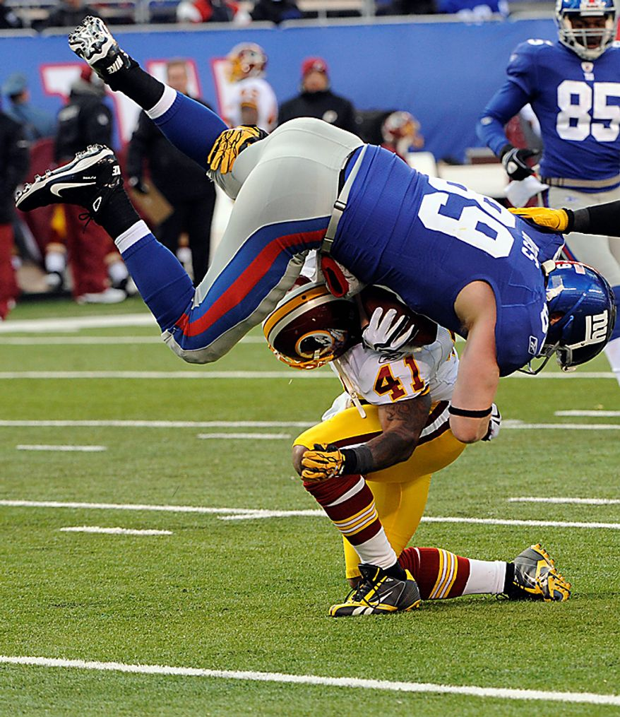 New York Giants tight end Kevin Boss (89) is tackled by Washington Redskins safety Kareem Moore (41) during the third quarter of an NFL football game at New Meadowlands Stadium, Sunday, Dec. 5, 2010, in East Rutherford, N.J. The Redskins lost the game 31-7. (AP Photo/Bill Kostroun)