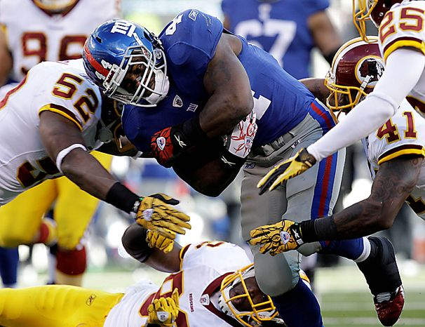 New York Giants running back Ahmad Bradshaw (44) is tackled by Washington Redskins linebacker Rocky McIntosh (52) and teammate Kareem Moore (41) during the second quarter of an NFL football game at New Meadowlands Stadium, Sunday, Dec. 5, 2010, in East Rutherford, N.J. (AP Photo/Kathy Willens)