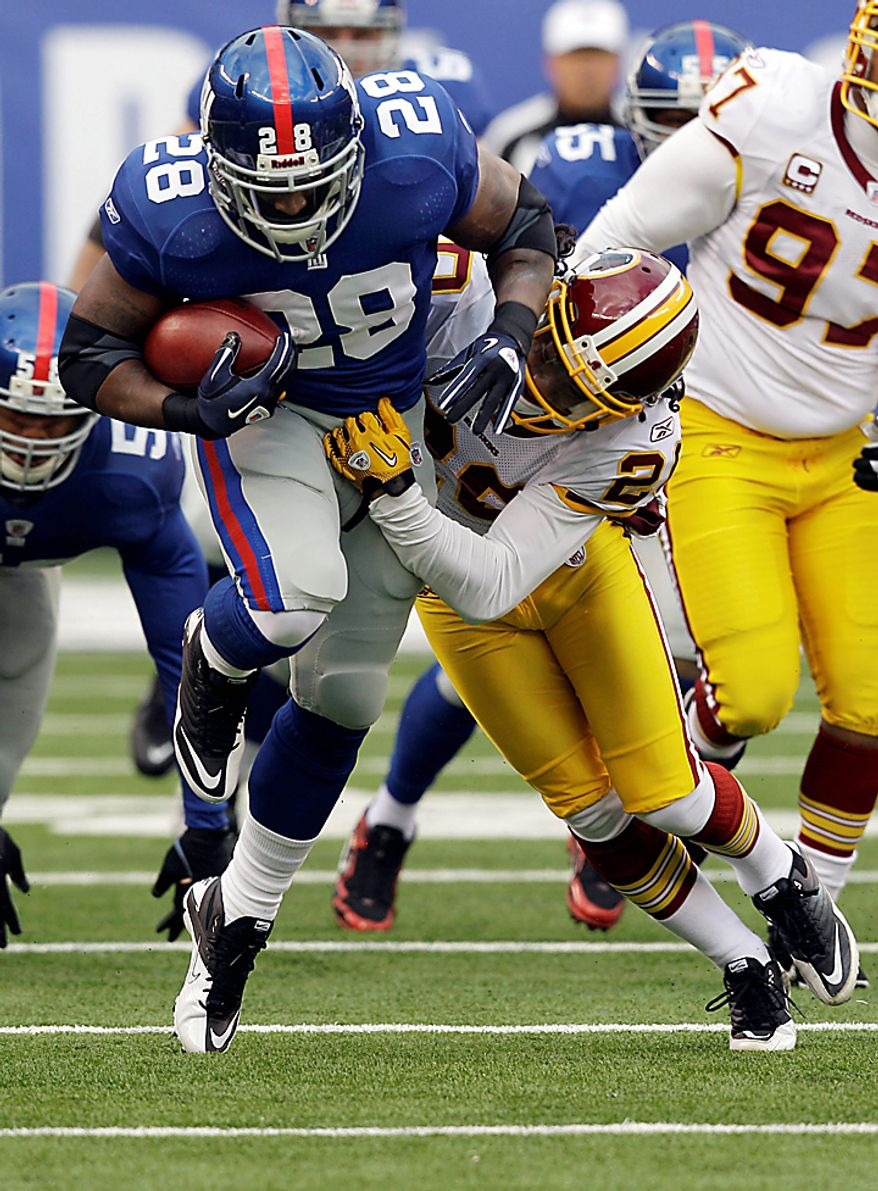 Washington Redskins cornerback Macho Harris (20) tackles New York Giants running back Danny Ware (28) during the first quarter of an NFL football game between the Washington Redskins and the New York Giants at New Meadowlands Stadium, Sunday, Dec. 5, 2010, in East Rutherford, N.J. (AP Photo/Kathy Willens)