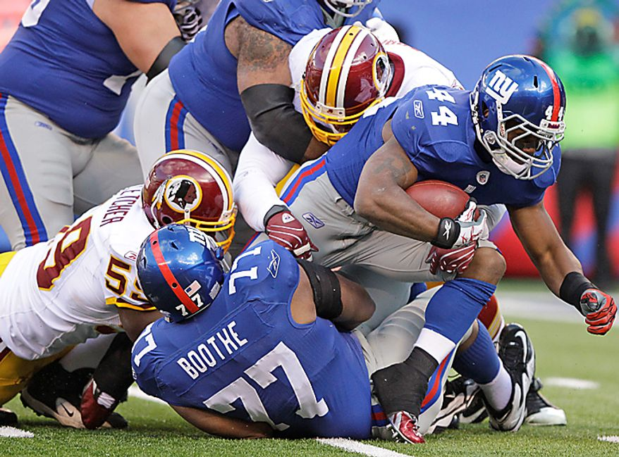 New York Giants running back Ahmad Bradshaw (44) is tackled by Washington Redskins linebacker London Fletcher (59) and Adam Carriker, blocked from view, as he steps over teammate Kevin Boothe (77) during the first quarter of an NFL football game at New Meadowlands Stadium, Sunday, Dec. 5, 2010, in East Rutherford, N.J. (AP Photo/Frank Franklin II)