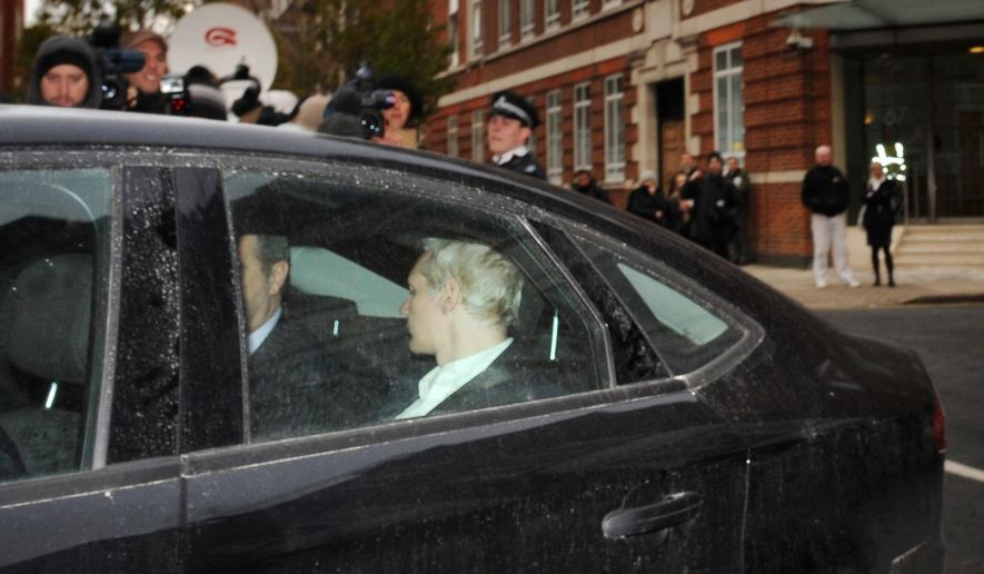 WikiLeaks founder Julian P. Assange (head turned) is driven into Westminster Magistrates Court in London on Tuesday after being arrested on a European Union warrant. He appeared for an extradition hearing in connection with sexual assault allegations in Sweden involving two women. He vowed to fight extradition and was ordered held.  (Associated Press)