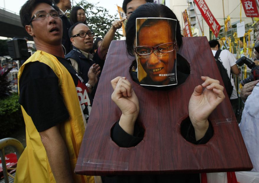 A pro-democracy protester wearing a mask of jailed Chinese dissident Liu Xiaobo protests outside the Chinese government liaison office in Hong Kong Sunday, Dec. 5, 2010. (AP Photo/Kin Cheung)