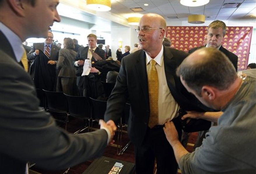 The new Minnesota Gophers head football coach Jerry Kill, center, met a reporter as a microphone was being attached to his belt during a news conference at TCF Stadium in Minneapolis, Minn., Monday, Dec. 6, 2010.  (AP Photo/Craig Lassig)