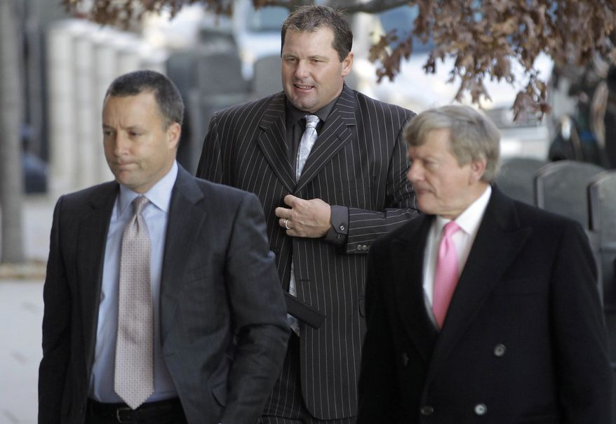 Former Major League Baseball pitcher Roger Clemens, center, accompanied by his lawyers, Michael Attanasio, left, and Rusty Hardin, arrives at court in Washington, Wednesday, Dec. 8, 2010, for an interim status conference on charges he lied to Congress when he denied taking steroids or other performance enhancing drugs. (AP Photo/Charles Dharapak)