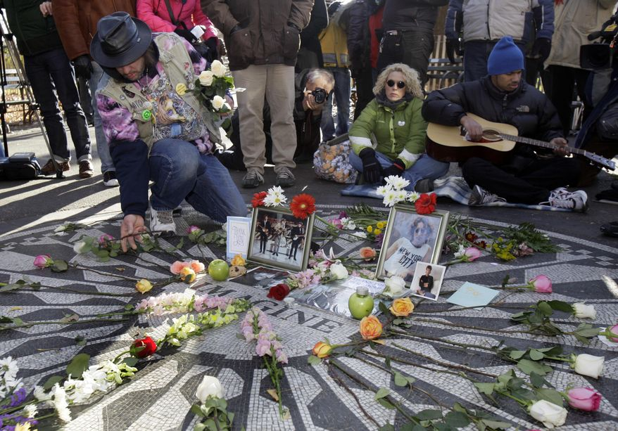 Gary Dos Santos (left) arranges flowers on the Imagine mosaic in the Strawberry Fields section of New York's Central Park on Wednesday, the 30th anniversary of the death of John Lennon. (Associated Press)