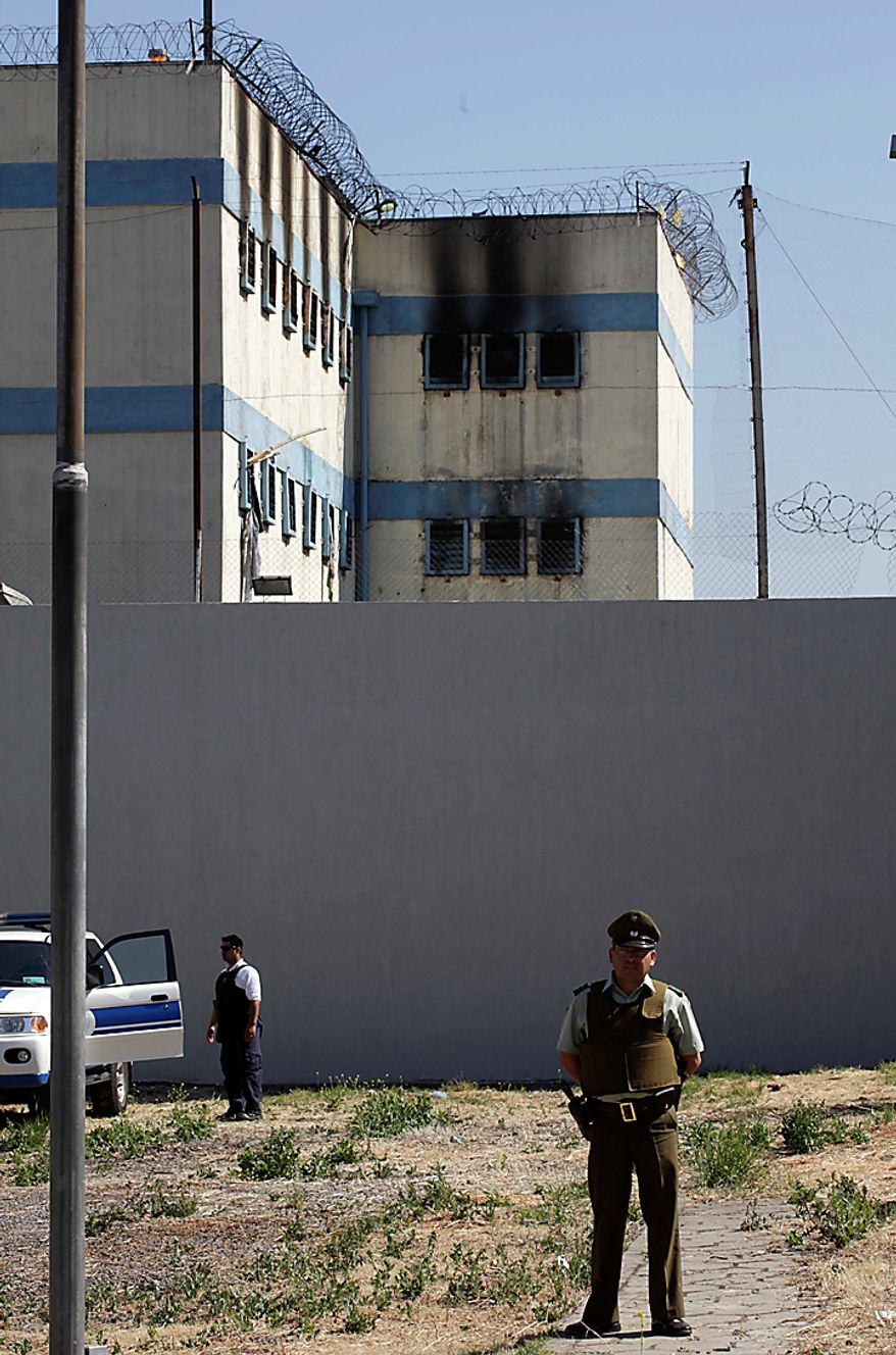 Police stand guard outside the San Miguel prison where a fire killed at least 81 prisoners in Santiago, Chile, Wednesday Dec. 8, 2010. The prison fire set off during a riot also seriously injured at least 14 others, officials said. (AP Photo/Aliosha Marquez)