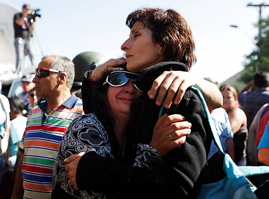 Relatives of inmates at San Miguel prison embrace as they wait for news after a fire killed at least 81 prisoners in Santiago, Chile, Wednesday Dec. 8, 2010. The prison fire set off during a riot also seriously injured at least 14 others, officials said. (AP Photo/Roberto Candia)