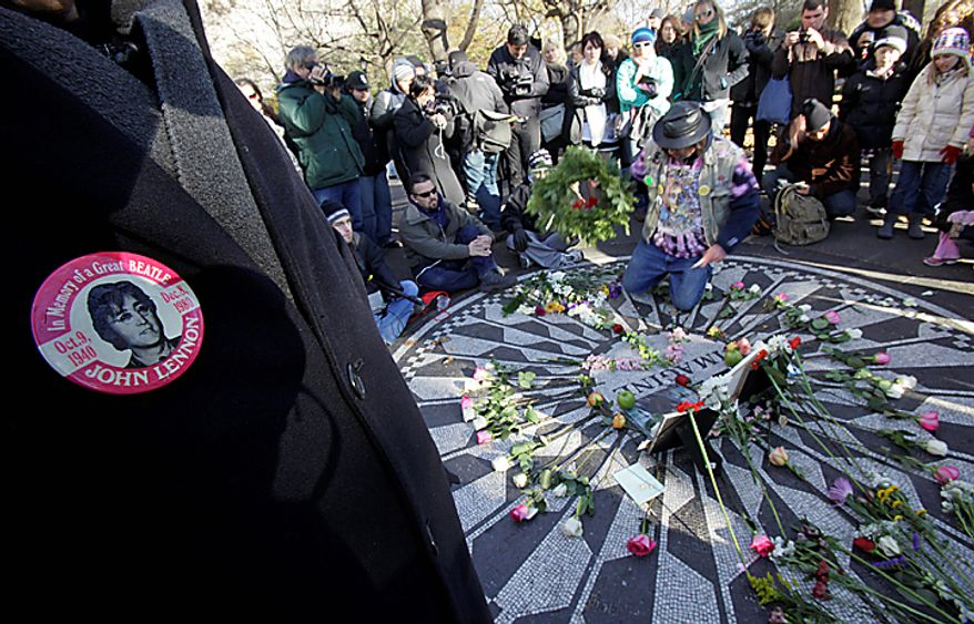 People surround the Imagine mosaic as a wreath is placed, in the Strawberry Fields section of New York's Central Park, Wednesday, Dec. 8, 2010, the 30th anniversary of the death of John Lennon. (AP Photo/Richard Drew)