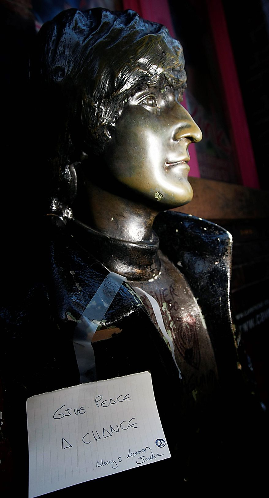 A note left on a statue of John Lennon outside the Cavern Pub in Mathew Street, Liverpool, England, Wednesday Dec. 8, 2010. Beatles fans planned to mark the 30th anniversary of John Lennon's death with a candlelit vigil at the city's European Peace Monument, which is dedicated to John Lennon. (AP Photo/Tim Hales)