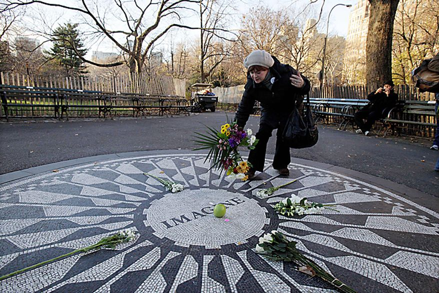 Robin Grinholz, of New York, lays flowers on the Imagine mosaic in the Strawberry Fields section of New York's Central Park,  Wednesday, Dec. 8, 2010, the 30th anniversary of the death of John Lennon. (AP Photo/Richard Drew)
