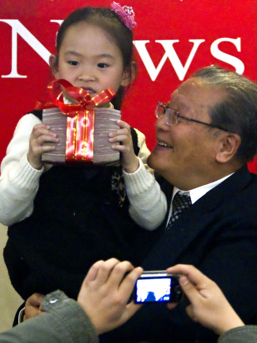 A girl shows a stack of prize money for the first Confucius Peace Prize awarded to former Taiwanese Vice President Lien Chan in Beijing on Thursday. The Chinese group awarded its own version of a peace prize, a move apparently intended to counter the Nobel committee's decision to honor imprisoned dissident Liu Xiaobo. (Associated Press)