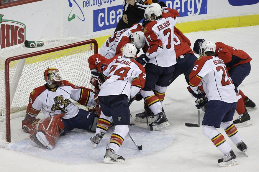 Florida Panthers goalie Tomas Vokoun (29), left, is knocked over by a swarm of defensive and offensive players during the first period of an NHL hockey game against the Washington Capitals at the Verizon Center in Washington, on Thursday, Dec. 9, 2010. (AP Photo/Jacquelyn Martin)