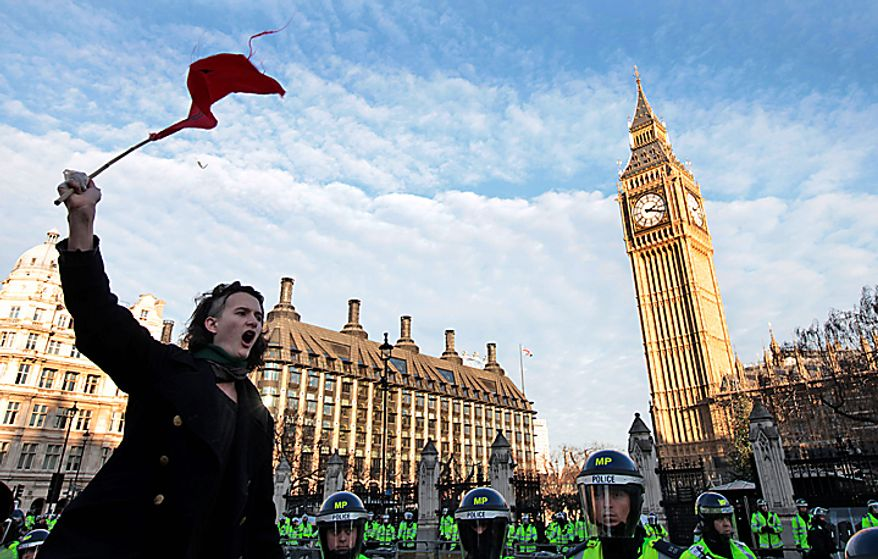 A student protests in Parliament Square in central London, Thursday, Dec. 9, 2010. Police clashed with protesters marching to London's Parliament Square as lawmakers debated a controversial plan to triple university tuition fees in England. (AP Photo/Lefteris Pitarakis)