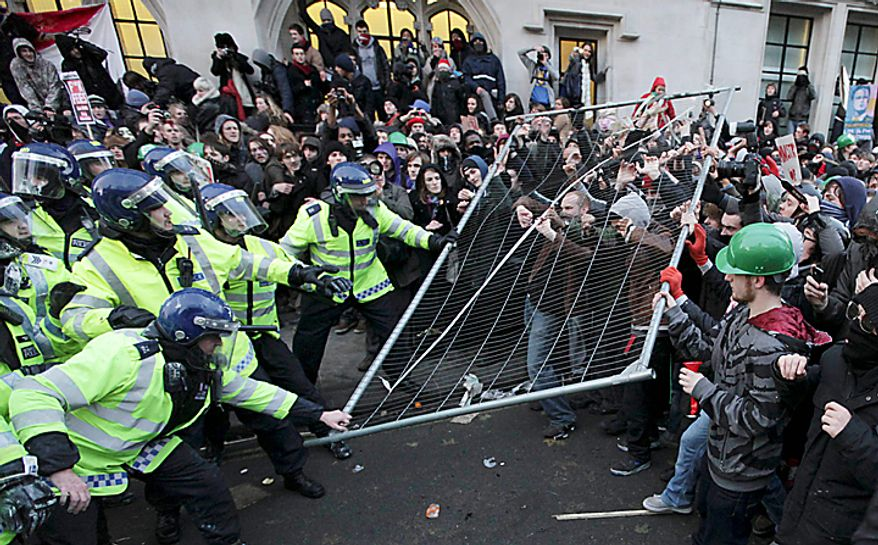 Protesters and police officers clash during a demonstration against an increase in tuition fees, on the edge of Parliament Square in London, Thursday, Dec. 9, 2010.  Police clashed with protesters marching to London's Parliament Square as lawmakers debated a controversial plan to triple university tuition fees in England.  (AP Photo/Matt Dunham)