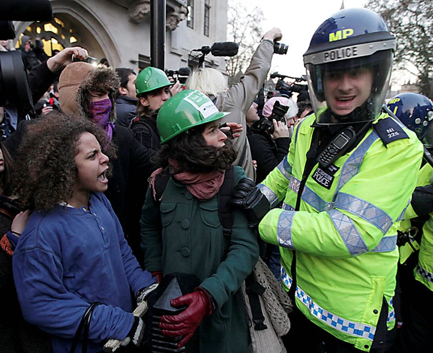 A police officer pushes a protester during a protest against an increase in tuition fees on the edge of Parliament Square in London, Thursday, Dec. 9, 2010.  Police clashed with protesters marching to London's Parliament Square as lawmakers debated a controversial plan to triple university tuition fees in England.  (AP Photo/Matt Dunham)