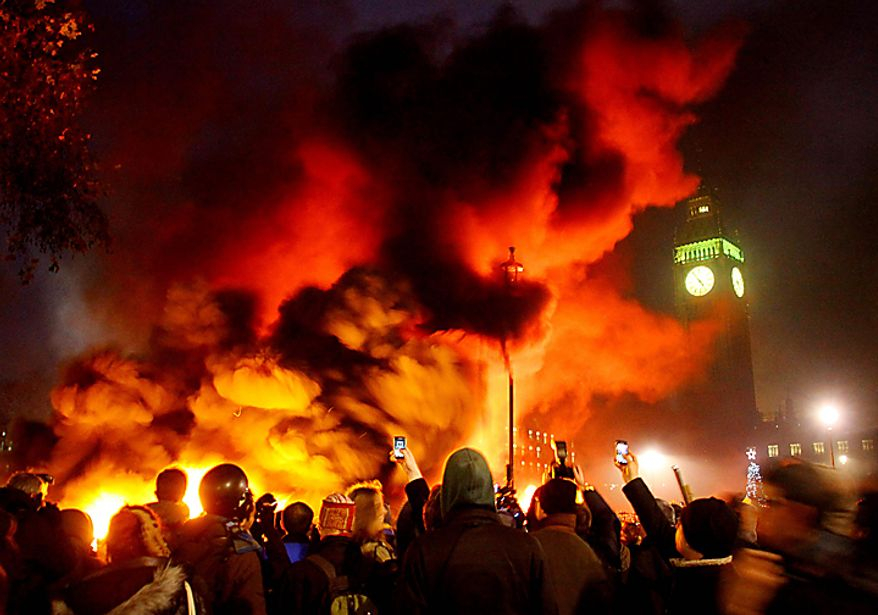 A fire burns in Parliament Square, Westminster, London, as students demonstrate  against planned tuition fee increases Thursday Dec. 9, 2010. Police with riot shields and batons pushed angry student protesters away from London's Parliament Square on Thursday as lawmakers debated a controversial plan to triple university tuition fees in England.  (AP Photo/Gareth Fuller/PA)