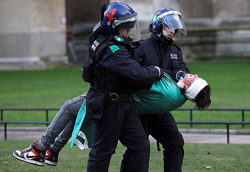British police medics carry an injured protester away, as thousands of students demonstrate outside the Houses of Parliament in London Thursday Dec. 9, 2010, during a protest against an increase in university tuition fees(AP Photo/Sang Tan)
