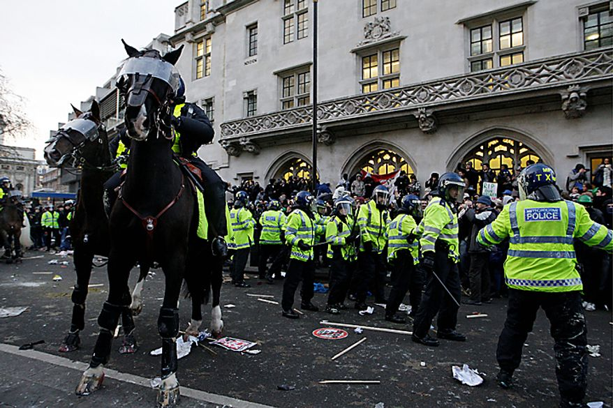 British police officers clash with protesters as thousands of students demonstrate outside the Houses of Parliament in London in a protest against an increase in tuition fees Thursday, Dec. 9, 2010. (AP Photo/Sang Tan)