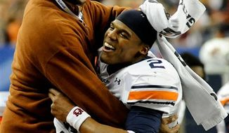 FILE - In this Dec. 4, 2010, file photo, Auburn quarterback Cameron Newton (2) leaps over the tackle of South Carolina's Akeem Auguste (3) during the second half of the Southeastern Conference Championship NCAA college football game at the Georgia Dome in Atlanta. Newton is among the four finalists for the Heisman Trophy.  (AP Photo/Butch Dill, File)