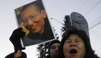 Protesters scream for the freedom of Nobel peace laureate Liu Xiaobo on Thursday, Dec. 9, 2010, outside the Chinese Embassy in Oslo, Norway. (AP Photo/John McConnico)