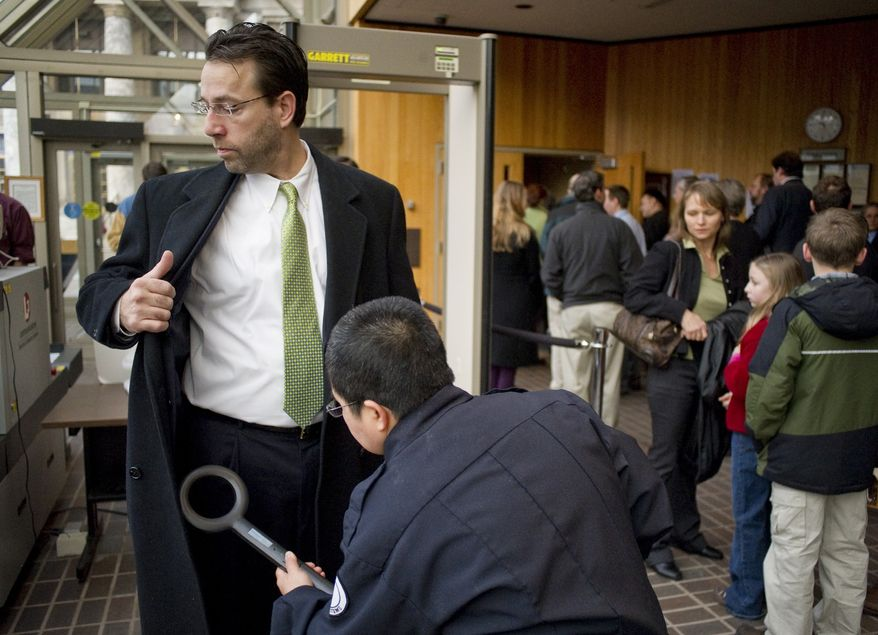 A security officer checks Joe Miller as he enters the Dimond Courthouse in Juneau, Alaska, on Wednesday, Dec. 8, 2010, for his court case against the State of Alaska in the U.S. Senate race with Sen. Lisa Murkowski. (AP Photo/The Juneau Empire, Michael Penn)