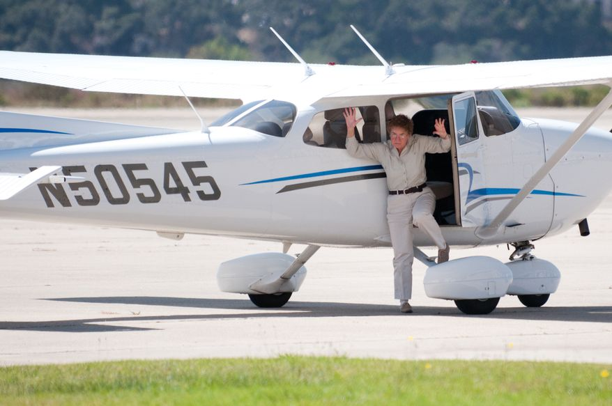 In this Aug. 28, 2010 photo, pilot Martha King steps out of a Cessna with her hands raised on the orders of police in Santa Barbara, Calif., as the plane was flagged as stolen by an aviation security computer system but the plane was actually owned by the pilots, two of the most famous aviation figures in the United States, John and Martha King. The Federal Aviation Administration's aircraft registry is missing key information on who owns about a third of the private and commercial planes in the U.S., a gap the agency fears could be exploited by terrorists and drug traffickers. (AP Photo/Santa Barbara News-Press, Robby Barthelmess)