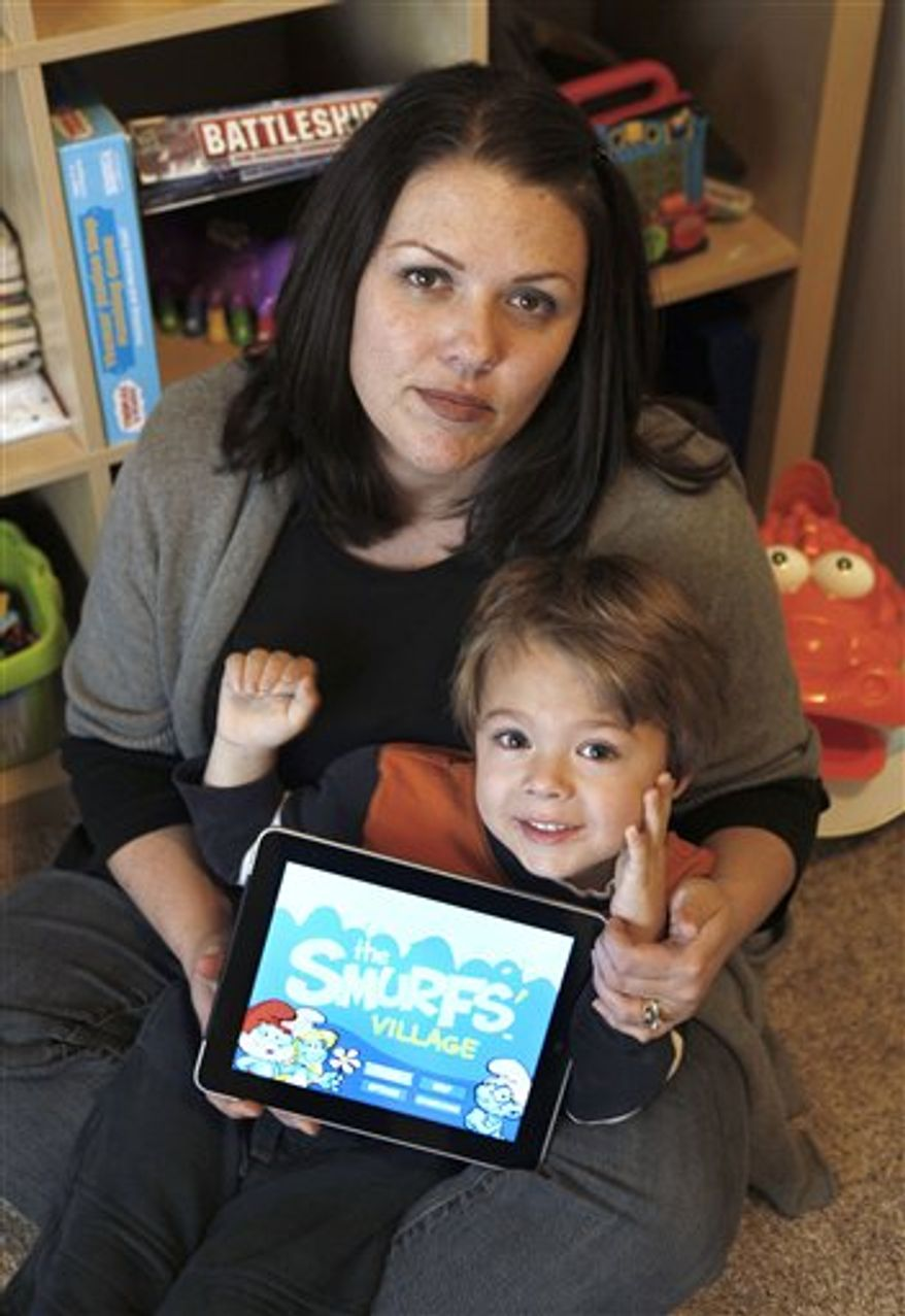 "In this photo taken Dec. 7, 2010, Sawyer Rummelhart, 4,  points to the ""The Smurf's Village"" app on his mothers iPad, at his families home in Gridley, Calif.(AP Photo/Rich Pedroncelli)"