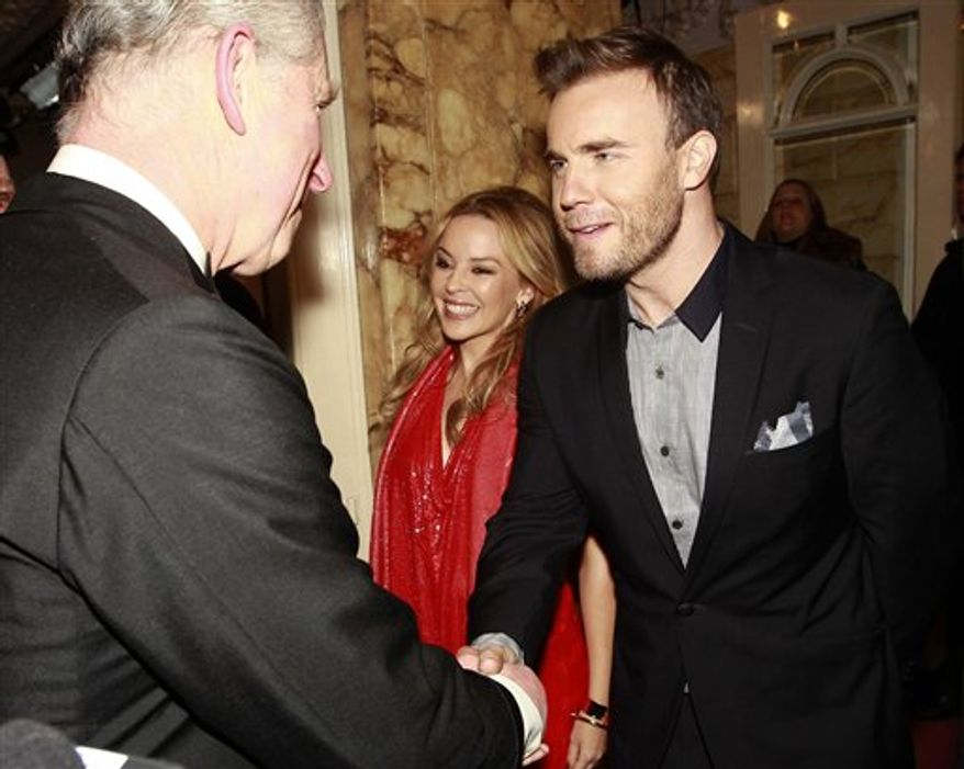 "Britain's Prince Charles shakes hands with Australian singer Kylie Minogue as he arrives to attend the Royal Variety Performance at the London Palladium, in London, Thursday Dec. 9, 2010. Shortly before, the car carrying the Prince and his wife the Duchess of Cornwall, had been attacked by rampaging students protesting against increased university fees. A group of up to 20 protesters, some chanting ""off with their heads!"" smashed a rear window and splashed white paint on the vehicle. The couple were visibly shaken, but unharmed. Man at centre is unidentified.(AP Photo/Eddie Keogh-pa) UNITED KINGDOM OUT: NO SALES: NO ARCHIVE:"