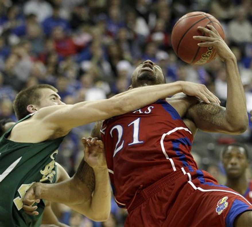 Kansas guard Tyshawn Taylor (10) puts up a shot under pressure from Colorado State guard Adam Nigon (12) during the first half of an NCAA college basketball game Saturday, Dec. 11, 2010, in Kansas City, Mo. (AP Photo/Charlie Riedel)