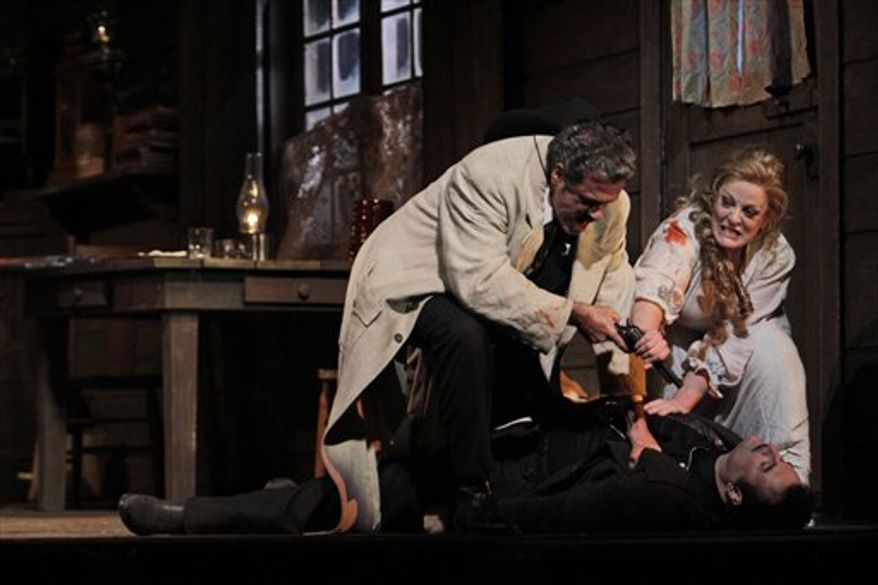 """This  Friday, Dec. 3, 2010 photo shows Lucio Gallo, left, performing as Jack Rance, alongside Marcello Giordani, top left, performing as Ramerrez and Deborah Voigt, top right, performing as Minnie during the final dress rehearsal of Giacomo Puccini's """"La Fanciulla del West"""", at the Metropolitan Opera in New York.  (AP Photo/Mary Altaffer)"""