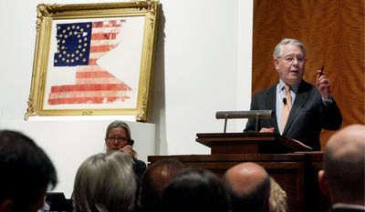 Auctioneer David Redden conducts bidding for the only U.S. flag not captured or lost during George Armstrong Custer's Last Stand at the Battle of Little Bighorn at Sotheby's in New York on Friday. (Associated Press)