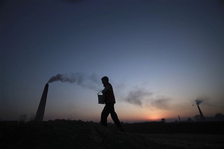 A boy walks past a brick factory on the outskirts of Jammu, India, Saturday, Dec. 11, 2010. After two decades of unbridled development, India is now the world's third-largest greenhouse gas emitter, with rivers the World Bank has described as fetid sewers and cities listed among the world's most polluted. India's environment Minister Jairam Ramesh suggested this week that India might commit to cutting emissions, saying all developing countries should consider doing so. (AP Photo/Channi Anand)
