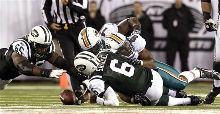 New York Jets quarterback Mark Sanchez (6) fumbles the ball as he is hit by Miami Dolphins linebacker Cameron Wake (91) during the second quarter of an NFL football game at New Meadowlands Stadium, Sunday, Dec. 12, 2010, in East Rutherford, N.J. The Jets recovered the fumble. (AP Photo/Bill Kostroun)