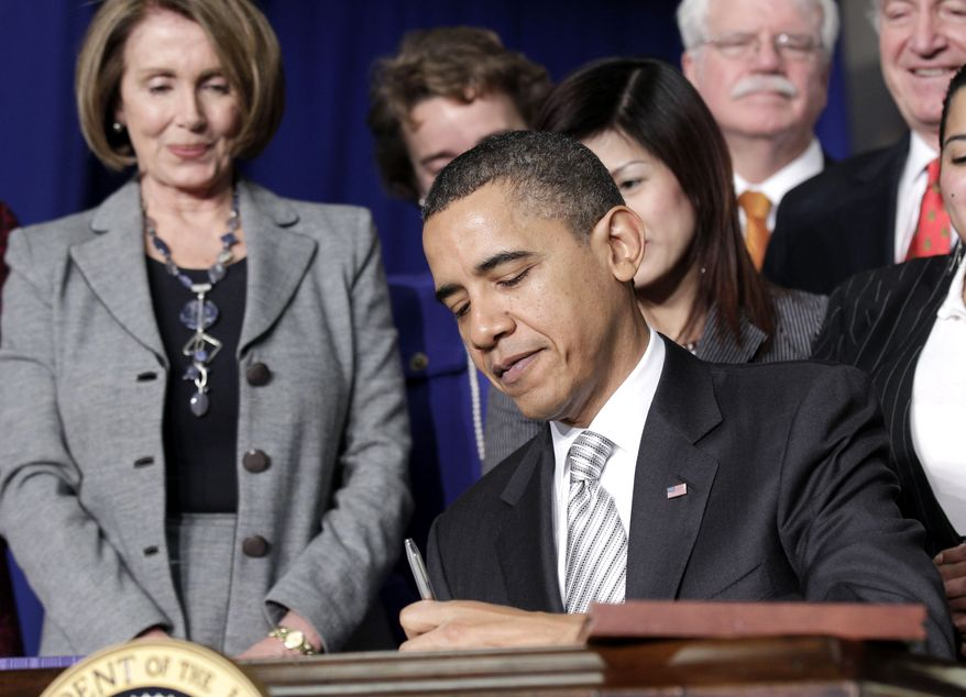 House Speaker Nancy Pelosi (left) and others look on as President Obama signs the Healthy, Hunger-Free Act of 2010 during a ceremony at Harriet Tubman Elementary School in Washington's Columbia Heights neighborhood on Monday, Dec. 13, 2010. (AP Photo/Pablo Martinez Monsivais)