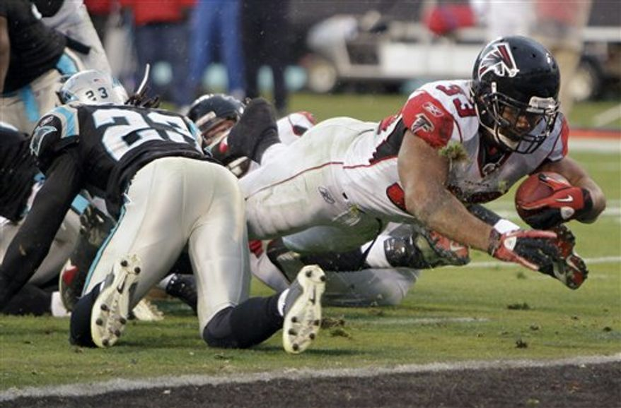 Atlanta Falcons' Michael Turner (33) dives in for a touchdown as Carolina Panthers' Sherrod Martin (23) defends during the second half of the Falcons' 31-10 win in an NFL football game in Charlotte, N.C., Sunday, Dec. 12, 2010. (AP Photo/Chuck Burton)