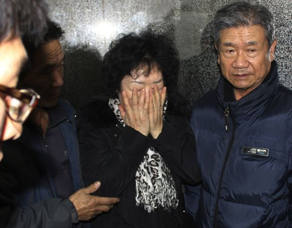Unidentified relatives of a crew member aboard a South Korean fishing boat that sank in the Antarctic Ocean arrive at the headquarters of Insung Corp., the owner of the ship, in Busan, South Korea, on Monday, Dec. 13, 2020. (AP Photo/Yonhap, Min Young-kyun)