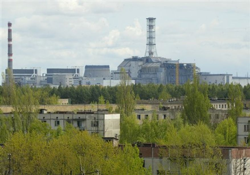 **FILE** In this photo from May 10, 2007, a general view of empty houses in the town of Pripyat are seen, with the closed Chernobyl nuclear power plant in the background. (Associated Press)
