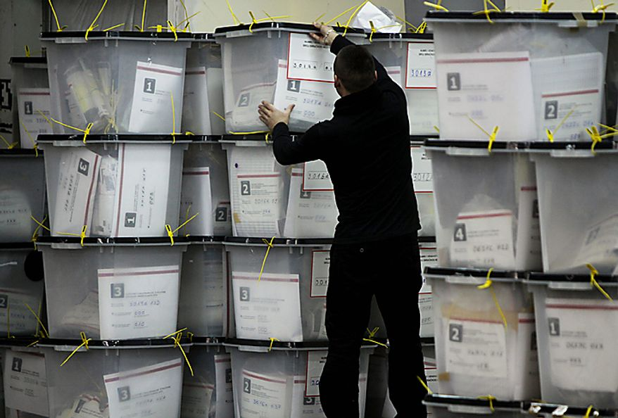Election official inpects ballot boxes in an Election Commission counting center in Kosovo Polje, Monday, Dec. 13, 2010. The election was Kosovo's first since its majority Albanian population split from Serbia in 2008. Exit polls showed Prime Minister Hashim Thaci's Democratic Party of Kosovo (PDK) won the most votes. (AP Photo/Visar Kryeziu)