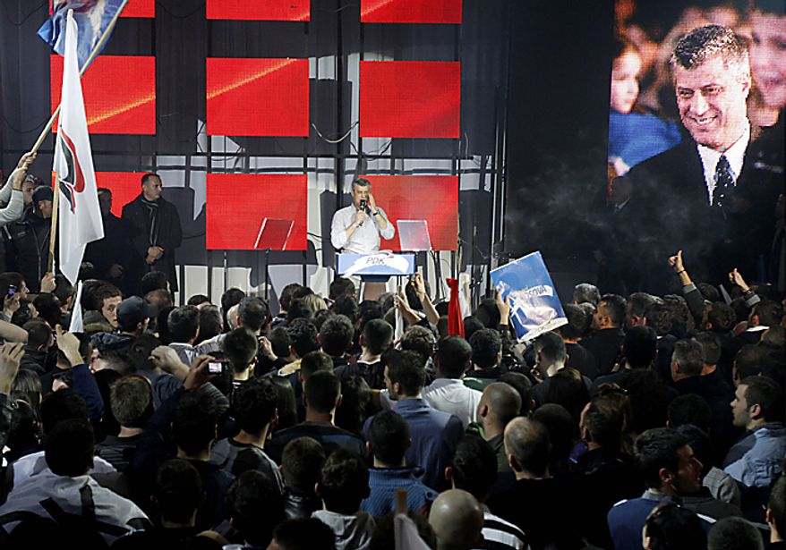 Kosovo's Prime Minister and leader of Democratic Party of Kosovo (PDK) Hashim Thaci, rear, speaks at his supporters celebrating victory in capital Pristina on Sunday, Dec. 12, 2010. Thaci has claimed victory in Kosovo's first general election since the province declared independence from Serbia, as an independent exit poll showed his Democratic Party of Kosovo 6 percentage points ahead of its rivals. (AP Photo/Visar Kryeziu)