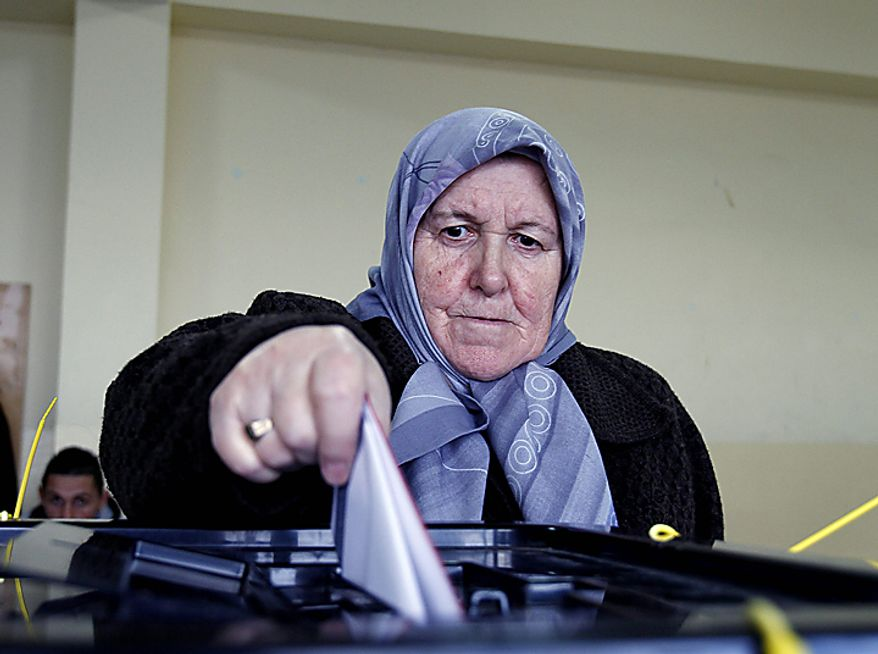 A Kosovo Albanian woman votes at a polling station during general elections in the town of Hajvalia on Sunday, Dec. 12, 2010.  Kosovars are voting Sunday in the first general poll since the country's declaration of independence from Serbia in 2008, a critical election already marred by ethnic tension that many fear will split the world's newest country. (AP Photo/Visar Kryeziu)
