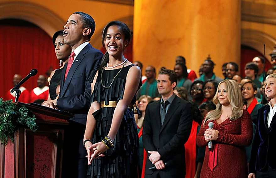 President Barack Obama, with his family first lady Michelle Obama, left, and their children Sasha Obama, obscured, and Malia Obama, third from left, are joined by from third right, Matthew Morrison, Mariah Carey, and host Ellen DeGeneres, during the Annual Christmas in Washington presentation, at the National Building Museum in Washington, Sunday, Dec. 12, 2010.   (AP Photo/Manuel Balce Ceneta)
