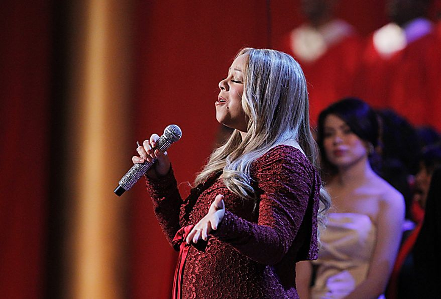 Singer Mariah Carey performs during the Annual Christmas in Washington presentation at the National Building Museum in Washington, Sunday, Dec. 12, 2010. Watching at the back is Miranda Cosgrove.  (AP Photo/Manuel Balce Ceneta)