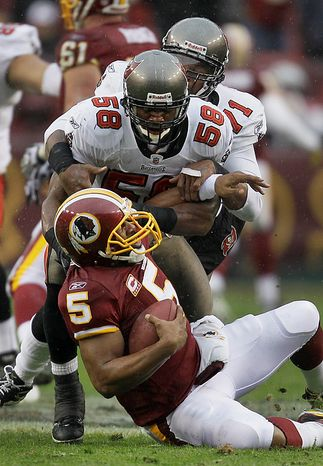 Washington Redskins quarterback Donovan McNabb (5) is sacked by Tampa Bay Buccaneers linebacker Quincy Black (58) and Michael Bennett, rear, during the first half of an NFL football game in Landover, Md., Sunday, Dec. 12, 2010. (AP Photo/Rob Carr)