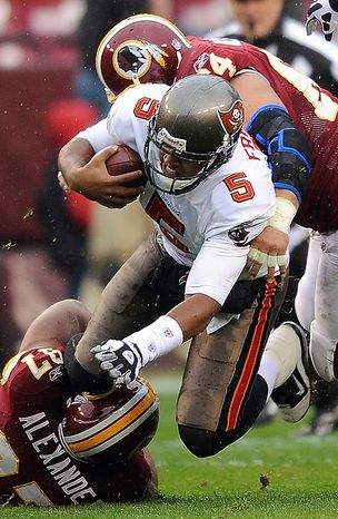 Tampa Bay Buccaneers quarterback Josh Freeman (5) is stopped by Washington Redskins linebacker Lorenzo Alexander, bottom left, and defensive end Kedric Golston, top right, during the first half of an NFL football game in Landover, Md., Sunday, Dec. 12, 2010. (AP Photo/Nick Wass)